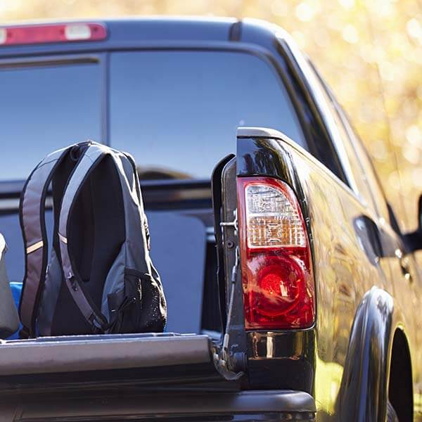 Black pickup truck with backpack on the back