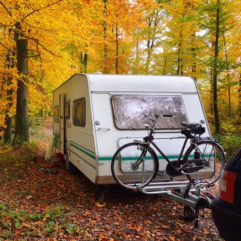 Caravan with attached bike in forest